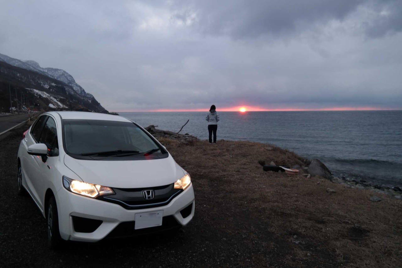 Sunset view of Sea of Japan. HONDA Fit, the rented car with my wife Stephanie in background.